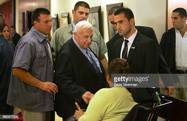 Israeli Prime Minister Ariel Sharon pauses to greet Israeli woman Simcha Benita a longtime activist for the rights of handicapped people as he walks...