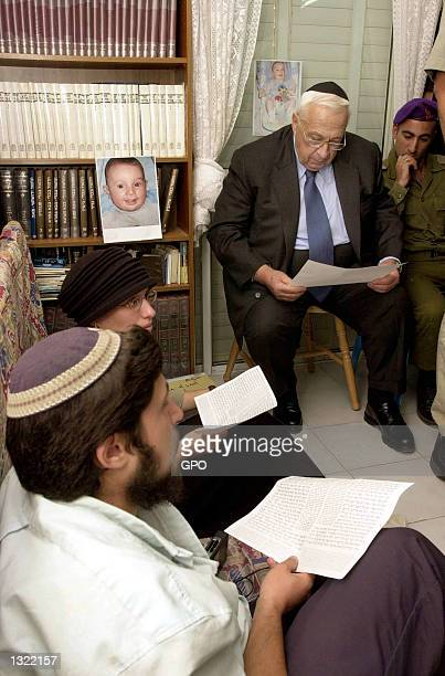 Israeli Prime Minister Ariel Sharon rear recites prayers with the family of Yehuda Haim Shoham as they sit in mourning June 17 2001 in the family''s...