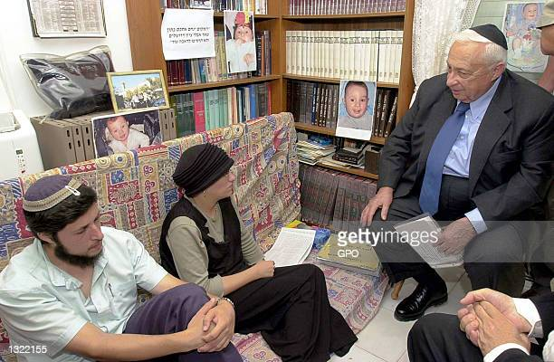Israeli Prime Minister Ariel Sharon, right, offers his sympathies to the family of Yehuda Haim Shoham, as they sit in mourning June 17, 2001 in the...
