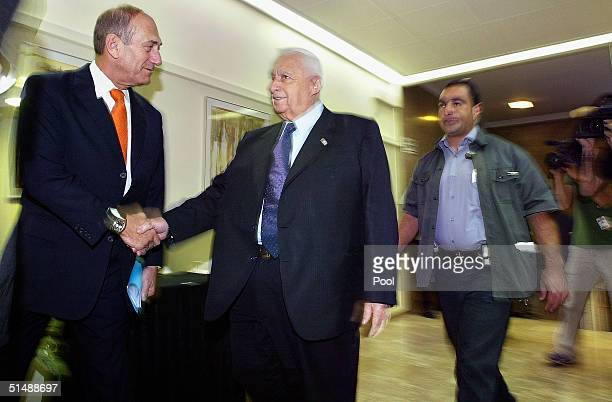 Israeli Prime Minister Ariel Sharon shakes hands with Deputy Prime Minister Ehud Olmert as Sharon arrives for his weekly cabinet meeting at his...