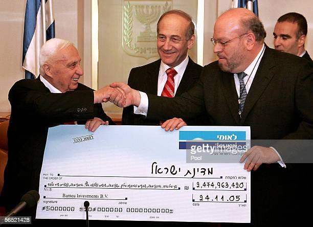 Israeli Prime Minister Ariel Sharon shakes hands with Ezra Merkin Managing partner for Gabriel Capital Group as Israeli Finance Minister Ehud Olmert...