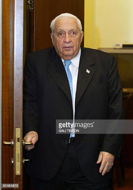 Israeli Prime Minister Ariel Sharon walks into a meeting at his Jerusalem office 22 March 2005 Four rebel MPs from Sharon's rightwing Likud party who...