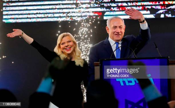 Israeli Prime Minister Benjamin Netanyahu accompanied by his wife Sara greets supporters on election night at his Likud Party headquarters in the...