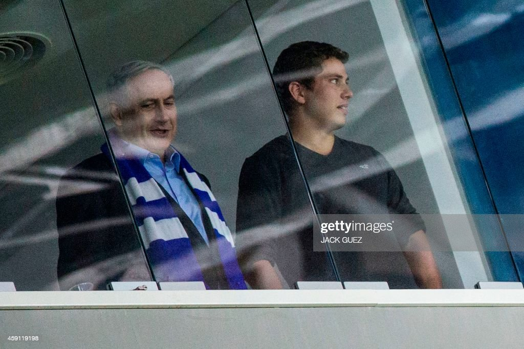 Israeli Prime Minister Benjamin Netanyahu (L) and his son Yair (R) look on while attending Euro 2016 Group B qualifying match against Israel and Bosnia-Herzegovina at the Sammy Ofer Stadium in the Israeli coastal city of Haifa on November 16, 2014.