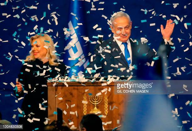 Israeli Prime Minister Benjamin Netanyahu and his wife Sara address supporters as confetti falls upon them at the Likud party campaign headquarters...