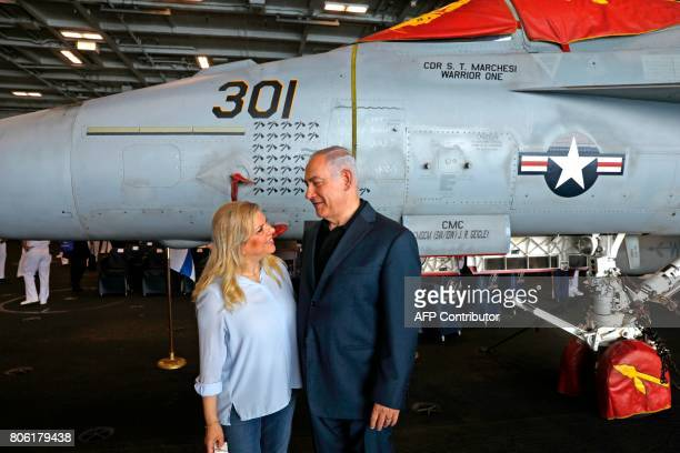 Israeli Prime Minister Benjamin Netanyahu and his wife Sara pose for a photo during a tour aboard the US aircraft carrier USS George H W Bush as it...