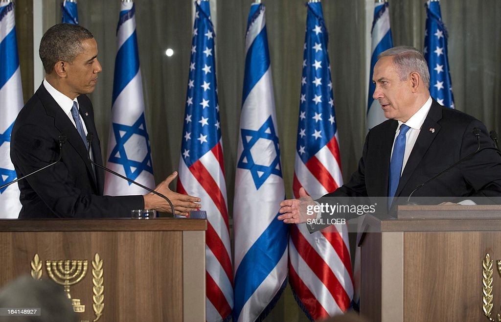 Israeli Prime Minister Benjamin Netanyahu (R) and US President Barack Obama reach out to shake hands during a joint press conference at the Prime Minister's Residence in Jerusalem, March 20, 2013, on the first day of Obama's three day trip to Israel and the Palestinian Territories. AFP PHOTO / Saul LOEB