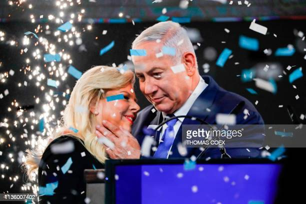 TOPSHOT Israeli Prime Minister Benjamin Netanyahu embraces his wife Sara as confetti and fireworks are blown during his appearance before supporters...