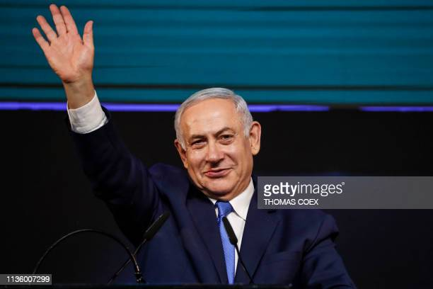 TOPSHOT Israeli Prime Minister Benjamin Netanyahu gestures as he appears before supporters at his Likud Party headquarters in the Israeli coastal...