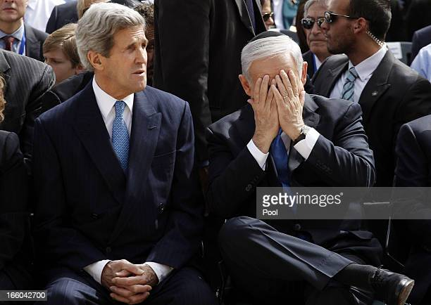 Israeli Prime Minister Benjamin Netanyahu gestures as he speaks to US Secretary of State John Kerry during the annual ceremony for Holocaust...
