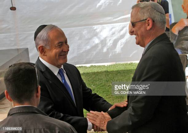 TOPSHOT Israeli Prime Minister Benjamin Netanyahu greets Benny Gantz leader of Blue and White party at a memorial ceremony for late Israeli president...