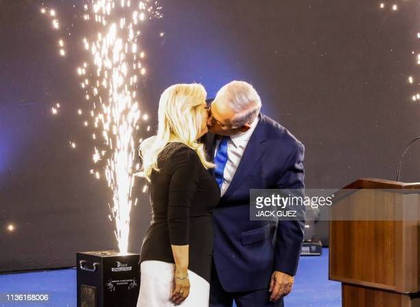 Israeli Prime Minister Benjamin Netanyahu kisses his wife Sara as he appears to supporters at his Likud Party headquarters in the Israeli coastal...