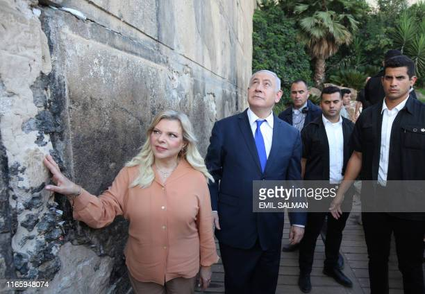 Israeli Prime Minister Benjamin Netanyahu looks up while his wife Sara touches the outside wall of the Cave of the Patriarchs also know for Muslims...