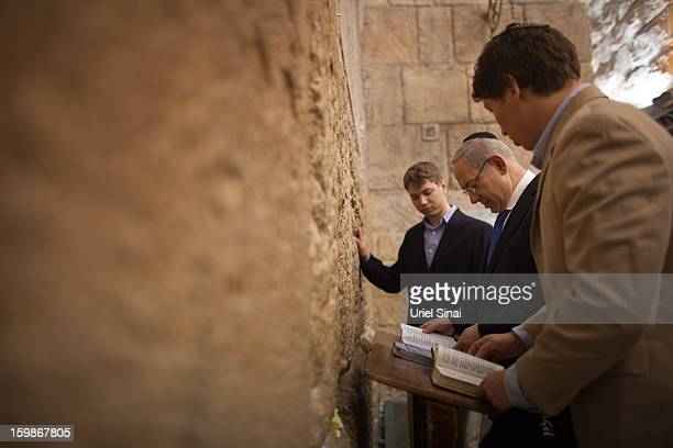 Israeli Prime Minister Benjamin Netanyahu prays with his sons Yair and Avner at the Western Wall Judaism holiest site on January 22 2013 in Jerusalem...