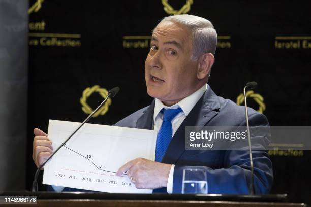 Israeli Prime Minister Benjamin Netanyahu presents a graph of 'Yisrael Beitienu' party last elections data during a press conference on May 30, 2019...