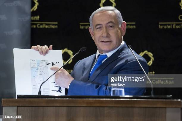Israeli Prime Minister Benjamin Netanyahu presents a map of Israel with the Golan Heights signed by US President Donald Trump during a press...