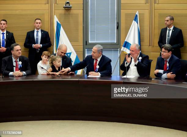 Israeli Prime Minister Benjamin Netanyahu reaches to pat the arm of the daughter of Justice Minister Amir Ohana , during a meeting of Likud party...