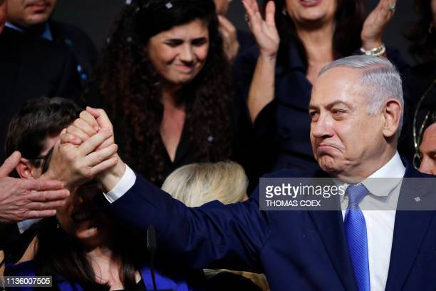 TOPSHOT Israeli Prime Minister Benjamin Netanyahu reacts as he shakes hands with someone after addressing supporters at his Likud Party headquarters...