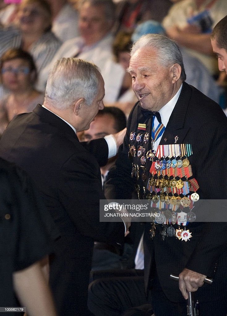Israeli Prime Minister Benjamin Netanyahu (L) shakes hands with a veteran during a ceremony honoring World War II veterans and marking the 65th anniversary of the Allied victory over Nazi Germany at the Armored Corps Memorial and Museum at Latrun Junction near Jerusalem on May 25, 2010.