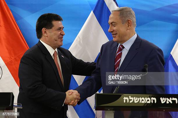 Israeli Prime Minister Benjamin Netanyahu shakes hands with Paraguayan President Horacio Cartes as they meet at his Jerusalem office on July 19 2016...