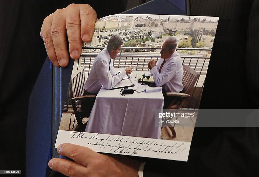 Israeli Prime Minister Benjamin Netanyahu shows a picture that was given to him as a gift by US Secretary of State John Kerry during a meeting in Jerusalem on May 23, 2013. Kerry flew in to Jerusalem as he kept up a push to bring Israelis and Palestinians back to peace negotiations amid a growing scepticism over his efforts.