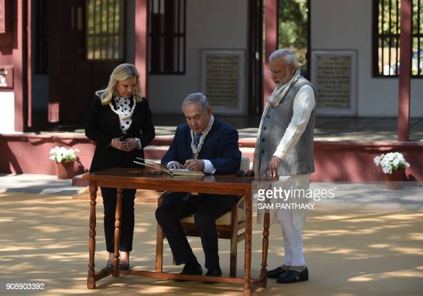 Israeli Prime Minister Benjamin Netanyahu signs a visitors book as his wife Sara Netanyahu and Indian Prime Minister Narendra Modi look on during a...