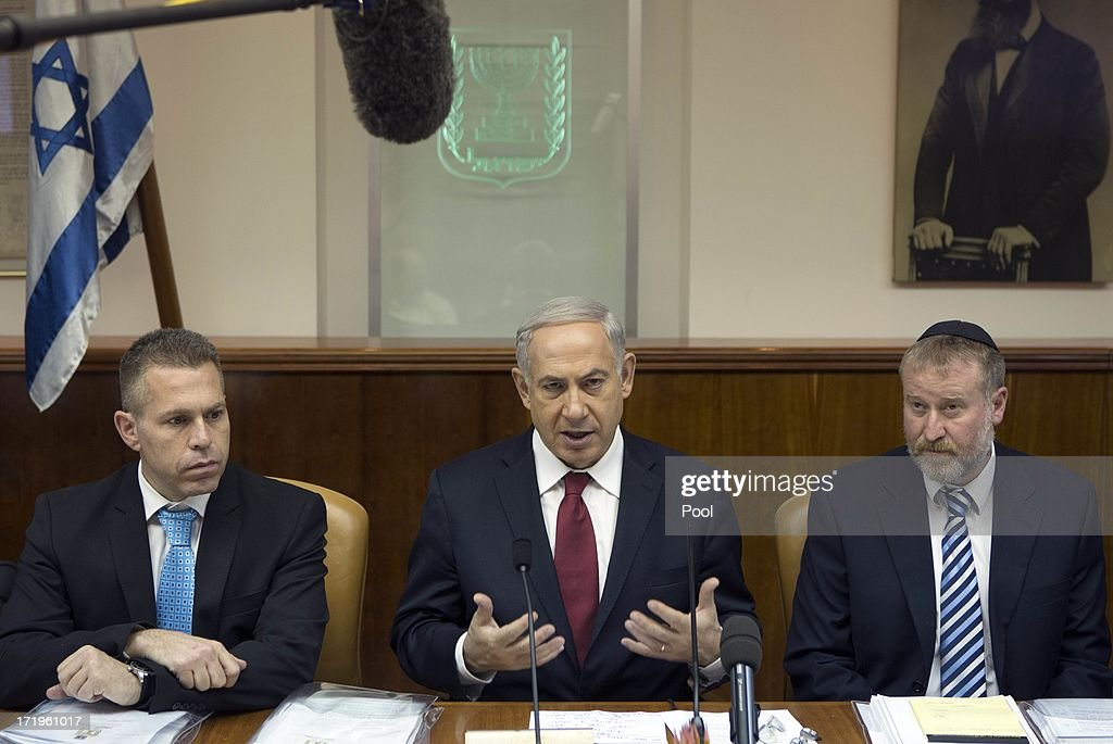 Israeli Prime Minister Benjamin Netanyahu (C) sits next to his Cabinet Secretary Avichai Mandelblit (R) and Communications Minister Gilad Erdan as he chairs the weekly cabinet meeting on June 30, 2013 in Jerusalem, Israel. Secretary of State John Kerry visited Israel this past week for peace talks.