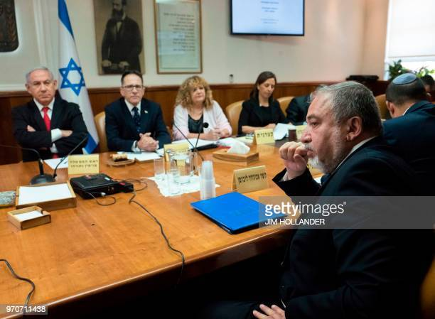 Israeli Prime Minister Benjamin Netanyahu sits opposite his Defense Minister Avigdor Lieberman during the weekly cabinet meeting in the prime...