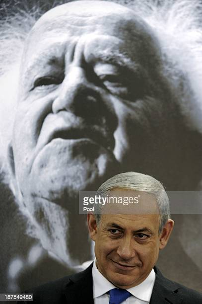 Israeli Prime Minister Benjamin Netanyahu sits under a portrait of the first Israeli prime minister David Ben Gurion as he speaks during a cabinet...