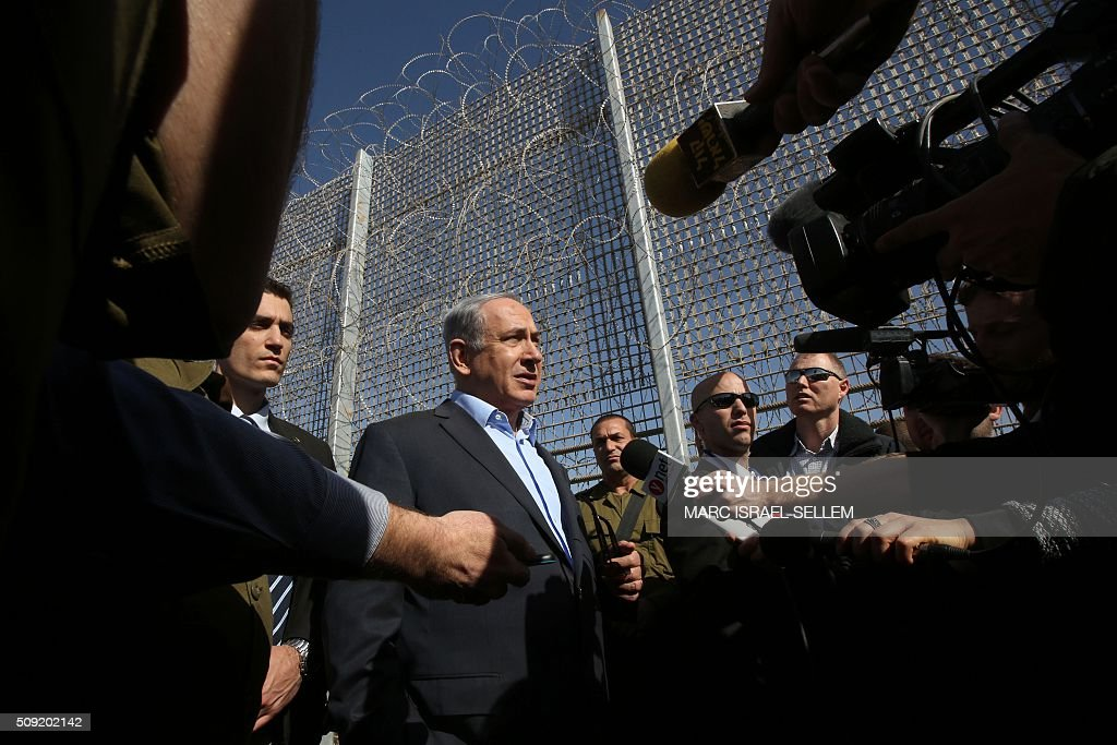 Israeli Prime Minister Benjamin Netanyahu (C) speaks to journalists during a visit to the construction site of a new military border fence between Israel and Jordan, on February 9, 2016. Israel has begun construction on a security fence along its border with Jordan, the defence ministry announced, its latest such barrier intended to keep out illegal migrants and militants. The barrier will be 30 kilometres (19 miles) long between the resort city of Eilat and the site of the Sands of Samar and will cost 300 million shekels ($75 million, 70 million euros), according Israeli authorities. / AFP / POOL / MARC