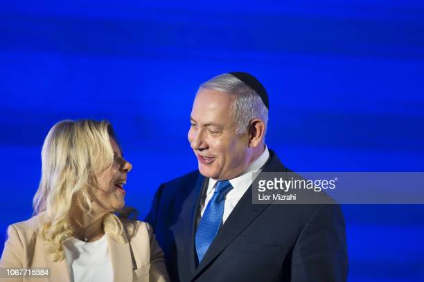 Israeli Prime Minister Benjamin Netanyahu stands by his wife Sara before lighting a stylised-menorah during the start of Hanukkah, the Jewish...