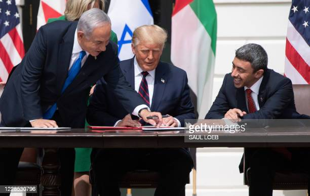 Israeli Prime Minister Benjamin Netanyahu, US President Donald Trump, and UAE Foreign Minister Abdullah bin Zayed Al-Nahyansmile as they participate...