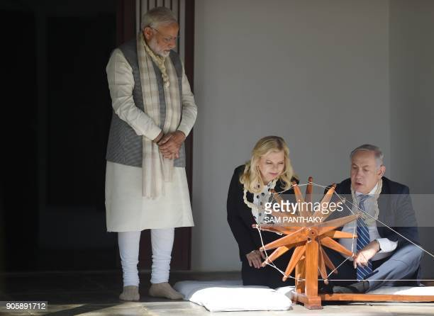 Israeli Prime Minister Benjamin Netanyahu uses a spinning wheel as his wife Sara Netanyahu and Indian Prime Minister Narendra Modi look on during a...