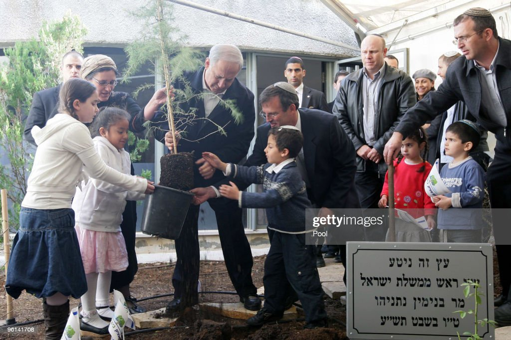 Israeli Prime Minister Benjamin Netanyahu (C) visited Kibbutz Kfar Atzion in Gush Etzion to plant a tree to mark the Tu B'Shvat festival January 24, 2010 in the West Bank. After a meeting with US Mideast envoy George Mitchell who pressed Israel to stop construction in settlement blocs Netanyahu was quoted saying 'The message is clear - we are here and will remain here. We are planting and building; this is an inseparable part of the State of Israel.'