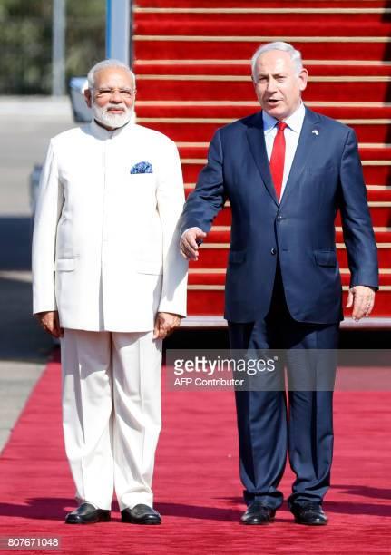 Israeli Prime Minister Benjamin Netanyahu walks with his Indian counterpart Narendra Modi during an official ceremoney at BenGurion International...