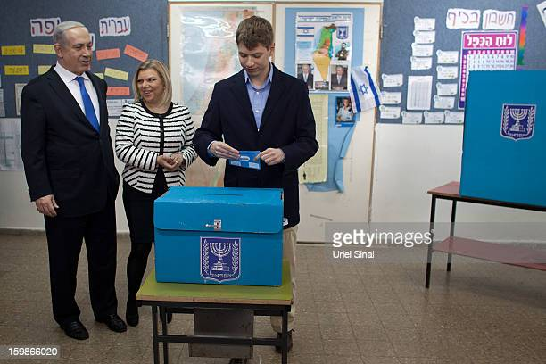 Israeli Prime Minister Benjamin Netanyahu watches his son Yair Netanyahu cast his ballot with by wife Sara Netanyahu at a polling station on election...