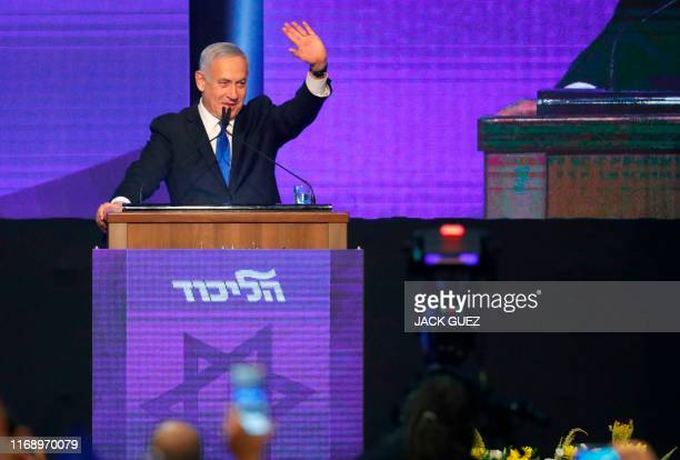 Israeli Prime Minister Benjamin Netanyahu waves as he addresses supporters at his Likud party's electoral campaign headquarters early on September...