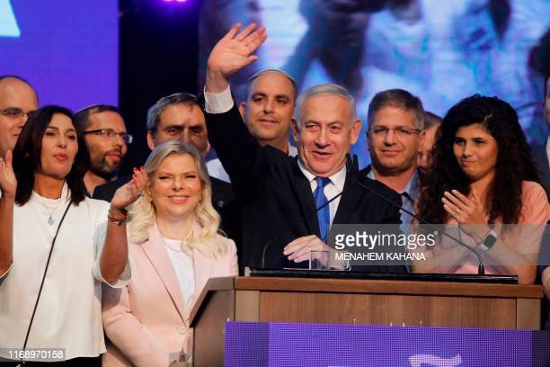 Israeli Prime Minister Benjamin Netanyahu waves to supporters alongside his wife Sara Netanyahu at his Likud party's electoral campaign headquarters...