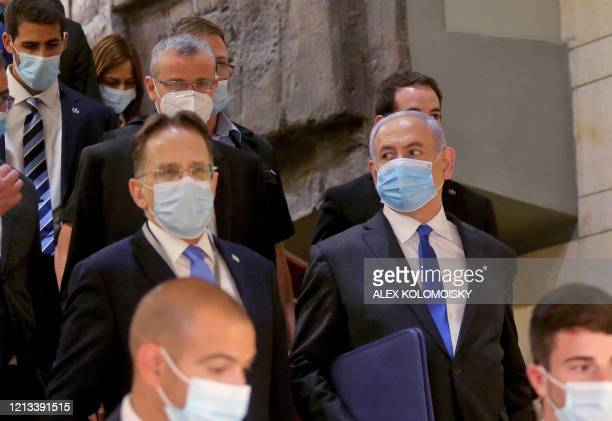 Israeli Prime Minister Benjamin Netanyahu , wearing a protective face mask, arrives for the swearing-in ceremony at Israel's parliament, the Knesset,...