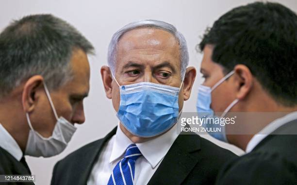 TOPSHOT Israeli Prime Minister Benjamin Netanyahu wearing a protective face maks speaks with his lawyer inside a courtroom at the district court of...
