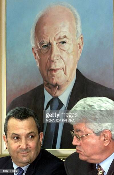 Israeli Prime Minister Ehud Barak and Foreign Minister David Levy sit under a picture of late Israeli Prime Minister Yitzhak Rabin during a Israel...