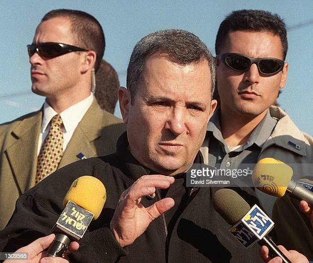 Israeli Prime Minister Ehud Barak flanked by secret service bodyguards addresses reporters during a visit to a major army base December 5 2000 on the...