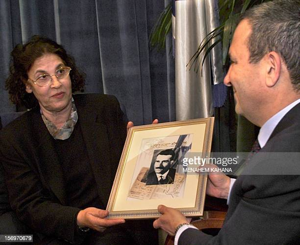 Israeli Prime Minister Ehud Barak receives 25 January 2000 a picture of a new postage stamp commemorating Eli Cohen an Israeli spy executed by Syria...