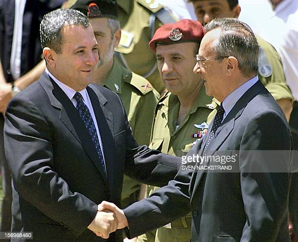 Israeli Prime Minister Ehud Barak shakes hands with outgoing Defence Minister Moshe Arens in Tel Aviv 07 July 1999, as Barak takes over the defence...