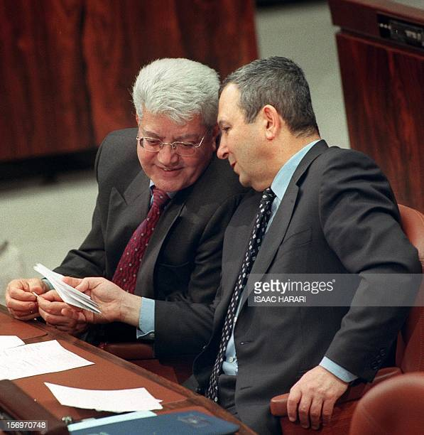 Israeli Prime Minister Ehud Barak talks to his Foreign Minister David Levy during a Knesset session in Jerusalem 07 March 2000 The two are due to...
