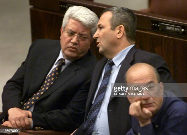 Israeli Prime Minister Ehud Barak talks to his Foreign Minister David Levy next to Israeli Education Minister Yossi Sarid 07 June 2000 during a...
