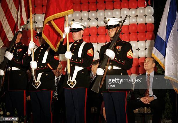 Israeli Prime Minister Ehud Olmert watches as US Marines stand at attention on a podium during a party in celebration of US Independence day at the...