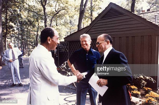 Israeli Prime Minister Menachem Begin shakes hands with Egyptian President Anwar Sadat at the start of the second trilateral meeting with US...