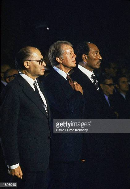Israeli Prime Minister Menachem Begin US President Jimmy Carter and Egyptian President Anwar Sadat stand at attention after the Camp David meeting...