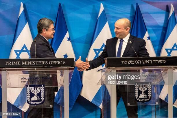 Israeli Prime Minister Naftali Bennett and Honduran President Juan Orlando Hernandez shake hands after their statements at the Prime Minister's...
